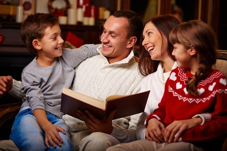 Cheerful family of four reading together at home photo