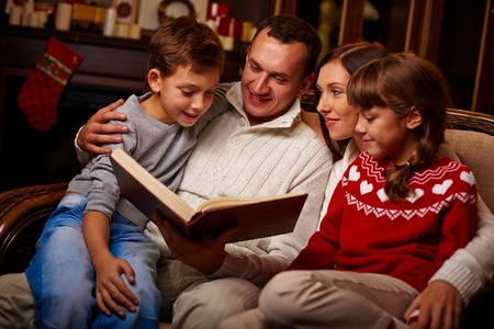 Modern family of four reading interesting tales at home photo