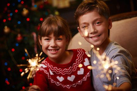 Two siblings with Bengal lights celebrating Christmas photo