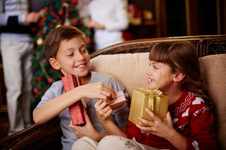 Glad boy and girl with Christmas presents in boxes photo