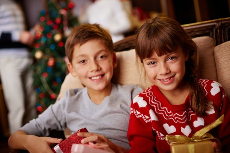 Adorable boy and girl with gifts looking at camera photo