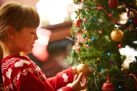 Cute little girl decorating Christmas firtree before holiday photo