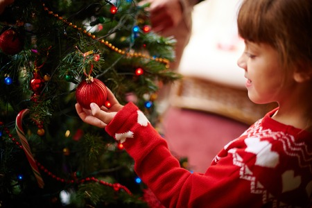 Cute little girl looking at red decorative toy bubble on xmas tree photo