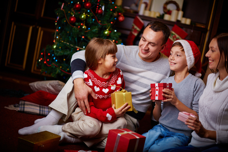 Joyful family with xmas gifts staying at home on holiday eve photo