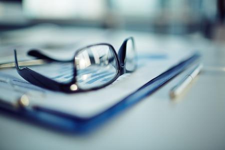 revisando documentos: Portapapeles con el documento, la pluma y gafas Foto de archivo