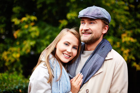 amorous woman: Smiling young woman embracing her husband and looking at camera