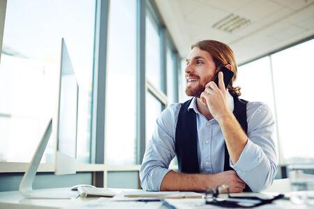 empleados trabajando: Gerente Hombre clientes consultar en el tel�fono en la oficina Foto de archivo