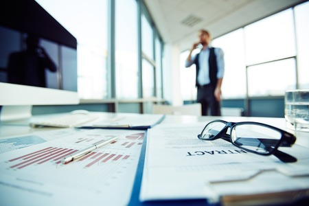 office environment: Business objects on desk with businessman calling on background