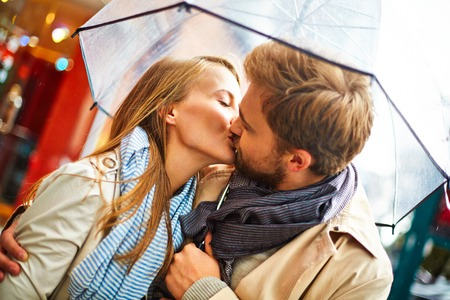 Amorous couple kissing under umbrella in urban environment