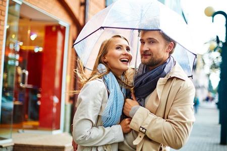 urban environment: Amorous valentines standing under umbrella in urban environment Stock Photo