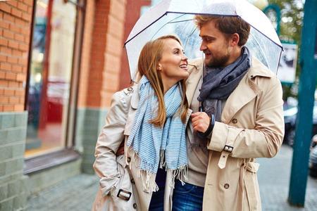 Boyfriend and girlfriend walking under umbrella in the city