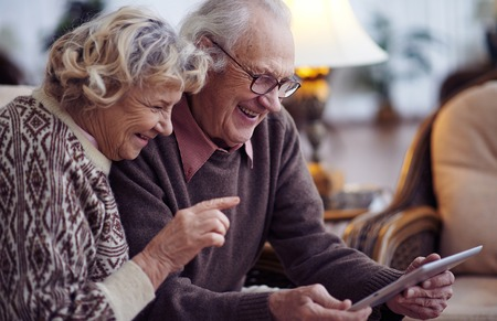 vejez feliz: Ancianos marido y mujer usando tableta digital en el hogar Foto de archivo