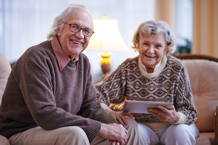 retirement  age: Happy senior couple looking at camera at home Stock Photo