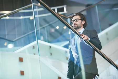 upstairs: Mature businessman in formalwear and eyeglasses going upstairs