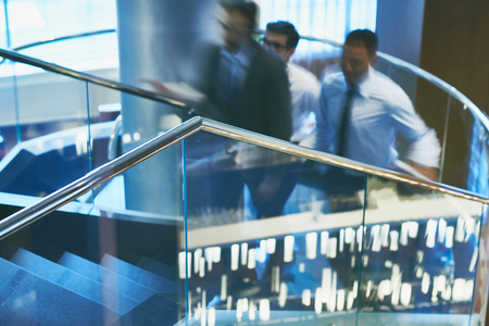 upstairs: Group of businessmen going upstairs in office building Stock Photo