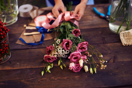 decorator: Hands of decorator tying bunch of flowers up with pink ribbon