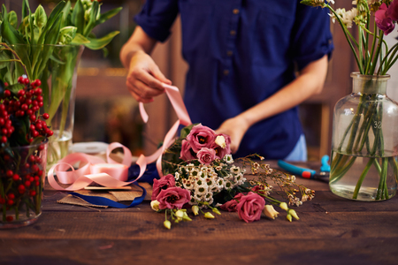 decorator: Female decorator tying flowers up with pink ribbon