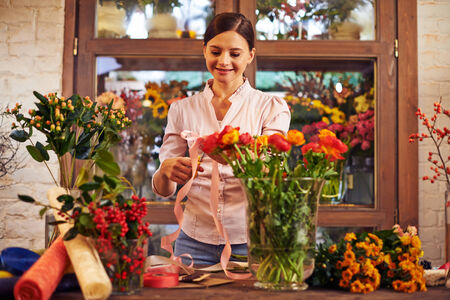 florist shop: Pretty florist making bouquets of fresh flowers and decorating them in shop Stock Photo