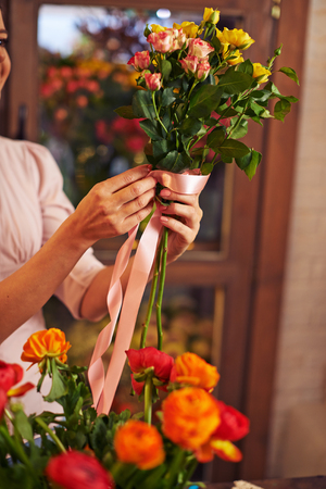 bunch up: Female decorator tying rose bunch up with silk ribbon Stock Photo
