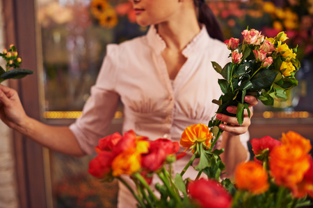 Florist with rose bunch working in shop Imagens