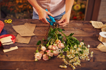 Female florist cutting stems of flowers in workshop Imagens