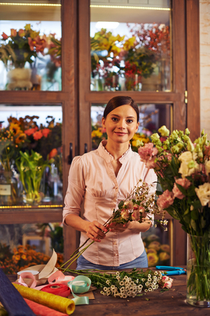 florist shop: Pretty florist working in shop of fresh flowers
