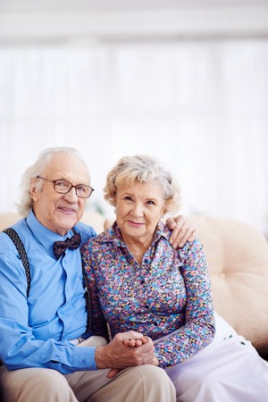 Elegantly dressed retired couple looking at camera