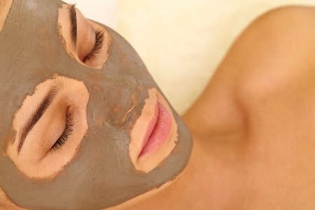 purifying: Relaxed woman having her face cleaned with clay mask