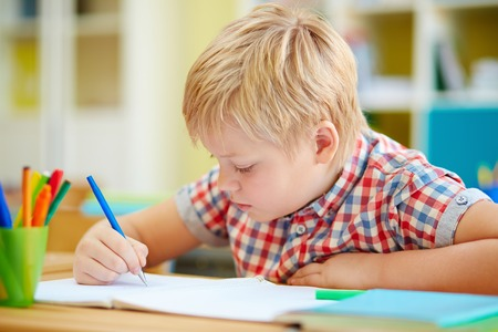 Little schoolboy writing in copybook at lesson Stock Photo