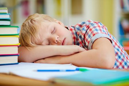 learner: Tired elementary learner sleeping in classroom