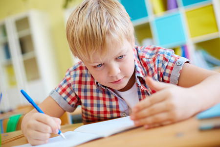 learner: Elementary learner cheating at lesson Stock Photo