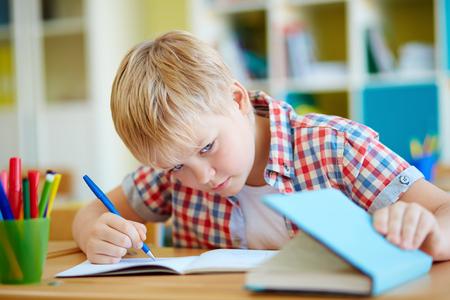 dishonest: Dishonest schoolboy looking the answer in book at lesson Stock Photo