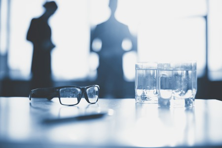 Eyeglasses and two glasses of water on desk photo