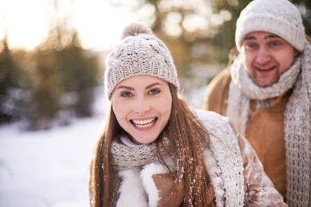 winterwear: Cute girl in winterwear looking at camera on background of her boyfriend in winter park