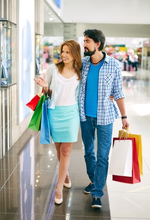 shopaholism: Portrait of young couple going in the mall and looking for new shopping