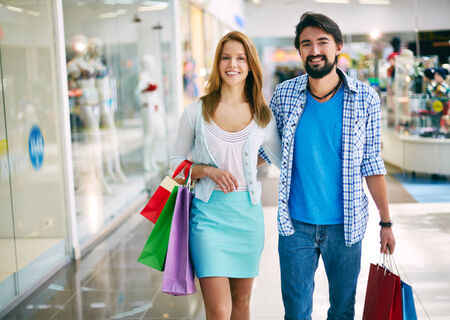 shopaholism: Affectionate young consumers shopping in the mall Stock Photo