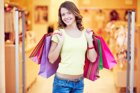 shopaholic: Curly-haired shopaholic with shopping bags looking at camera