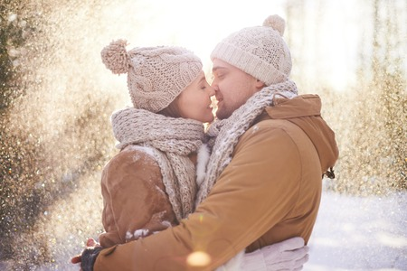 couple winter: Young dates in winterwear kissing in snowfall Stock Photo