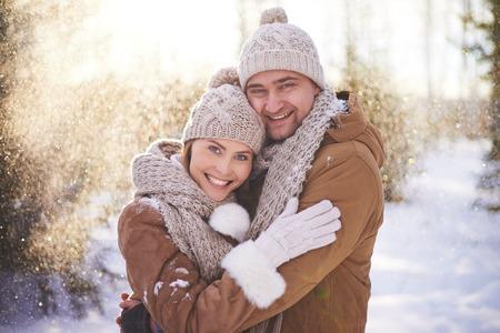 Amorous couple in winterwear embracing in snowfall Фото со стока