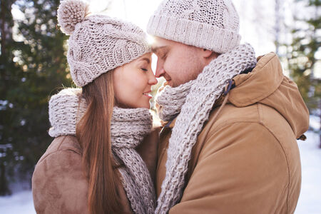 winterwear: Amorous dates in winterwear touching by noses outdoors