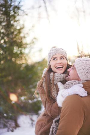 amorous woman: Cheerful couple in winterwear having fun in natural environment