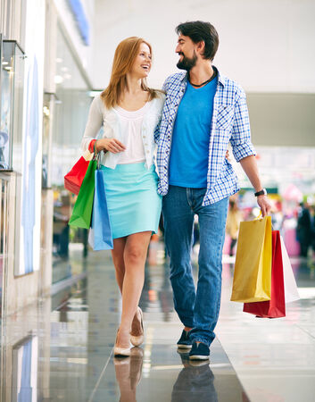 shopaholism: Portrait of happy couple with paperbags going in the mall Stock Photo