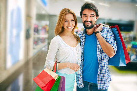 shopaholism: Affectionate shopaholics with paperbags looking at camera