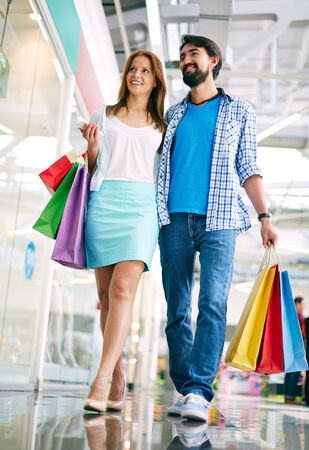 shopaholism: Young husband and wife shopping in the mall Stock Photo