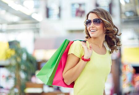 shopaholic: Young shopaholic in sunglasses enjoying her favorite pastime