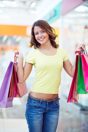 shopaholic: Happy female shopaholic with shopping bags looking at camera Stock Photo
