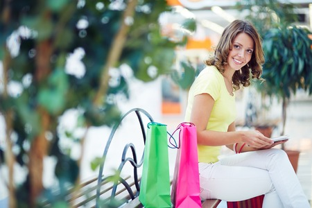 buyer: Feminine buyer resting on bench in the mall after shopping