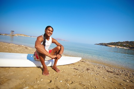 philippine adult: Happy surfer sitting on the beach