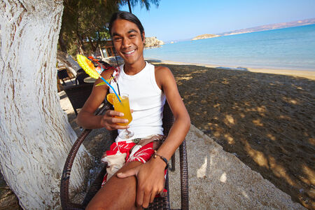 philippine adult: Happy Latino man having a drink in summer cafe at resort Stock Photo