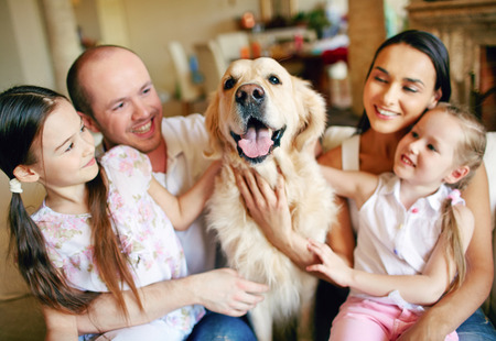 Cute girls and their parents cuddling dog